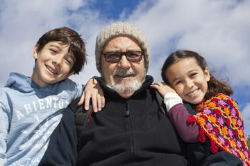 Abuelo flanqueado por nieto y nieta