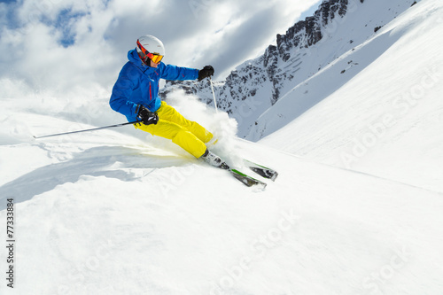 Male skier on downhill freeride with sun and mountain view - 77333884