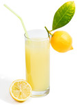 Glass of lemon juice and fruit with leaves