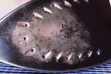 Flat iron with burnt mark on fabric background