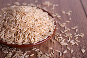 Brown rice on plate on wooden background