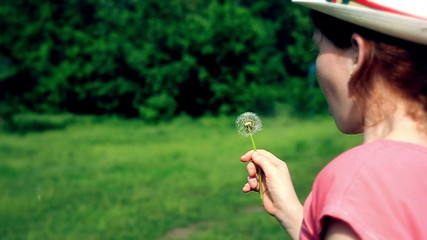 The red cute girl blows on the dandelion 3