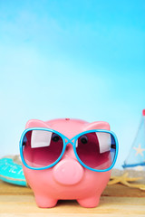 Piggy bank with sunglasses on wooden table, outdoors