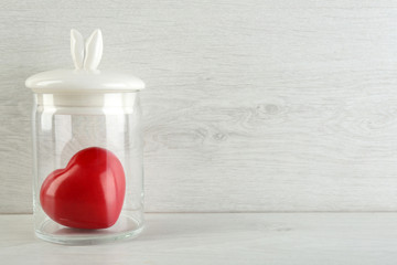 Decorative heart in glass jar on light background