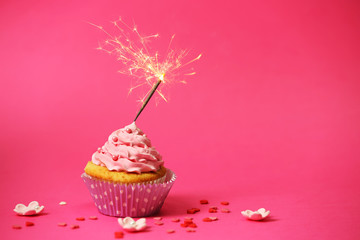 Cupcake with sparkler on pink background