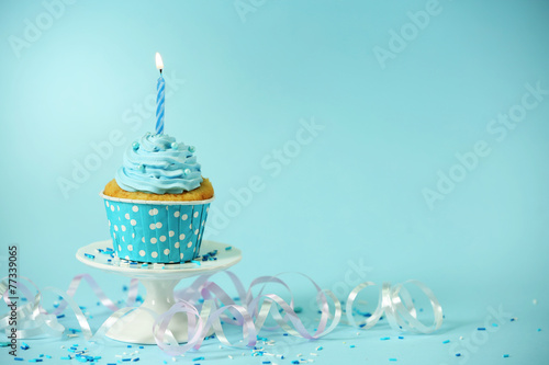 Delicious cupcake on table on blue background - 77339065