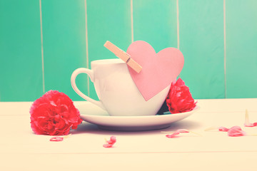 Coffee cup with pink heart tag and carnations