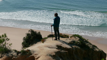 Man Stands on a Cliff Above the Ocean and Drinking Water