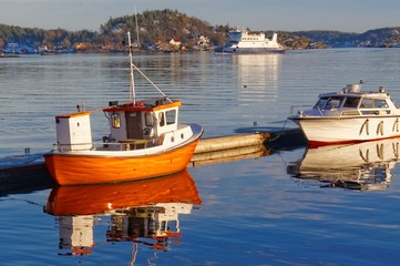 Small orange fishing boat with reflection in the water