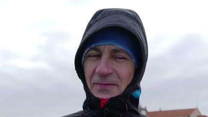 Adult Men Resist Hurricane Winds, closeup