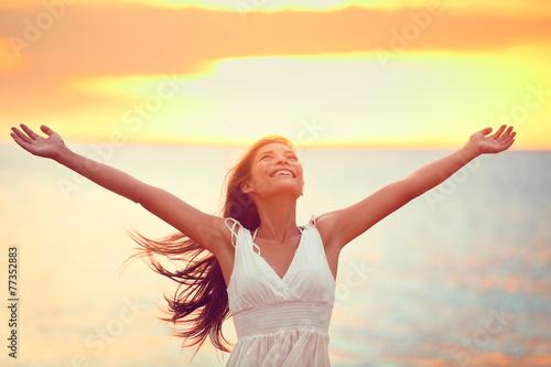 Free happy woman praising freedom at beach sunset