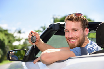 Man driving new rental car showing keys happy