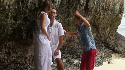 bride and groom stand under cliff and man explains groom how to
