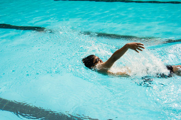 young man swimming in backstroke in a pool.