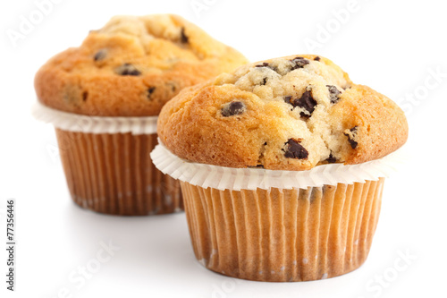 Two light chocolate chip muffins in wax liner on white. - 77356446