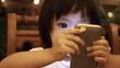 Asian baby looking mobile phone