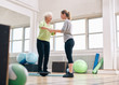 Trainer helping senior woman on bosu balance training platform - 77361447