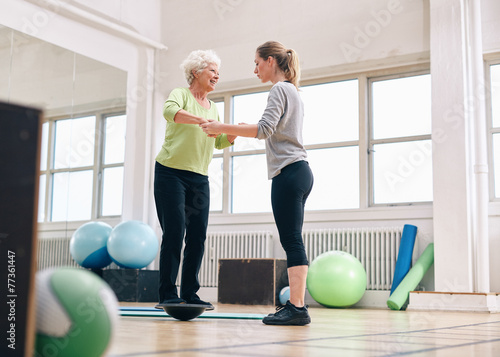 Trainer helping senior woman on bosu balance training platform - 77361447