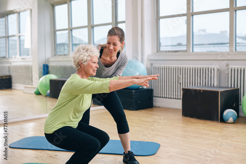 Elderly woman doing exercise with her personal trainer - 77361655