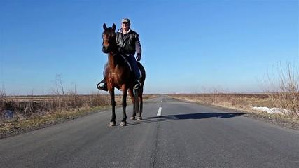 Man is riding a horse on rural landscape, road of asphalt