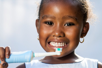 Cute little afro girl holding electric toothbrush.
