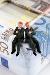 Manager-Figuren sitzen auf Paket von Euro-Banknoten