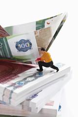 Figürchen auf Bündel von Euro-Banknoten mit Papier Boot