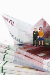 Paarfigürchen auf Bündel von Euro-Banknoten mit Papier Boot