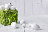Fototapety Easter eggs in a green basket on a white table