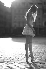 Slender ballerina standing on tiptoes in the street, monochrome