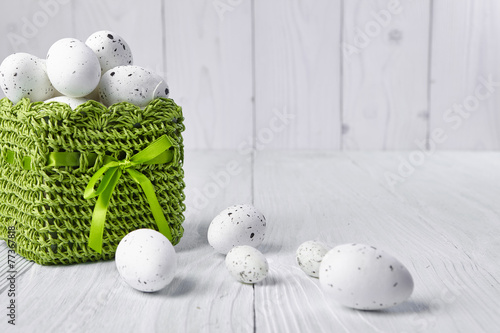 Easter eggs in a green basket on a white table - 77367818