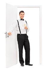 Elegant guy standing by a door and holding wine
