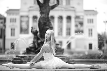 Beautiful ballerina doing a split outdoors, monochrome