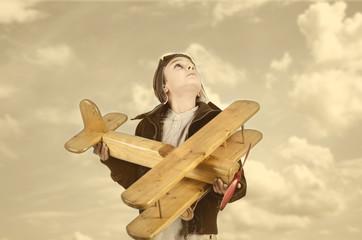 Kind mit Holzflugzeug