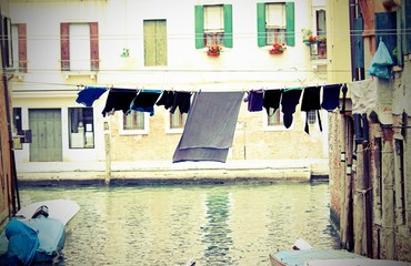 Sheets and drying laundry on the Canal full of water in Venice