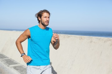Fit man jogging on promenade