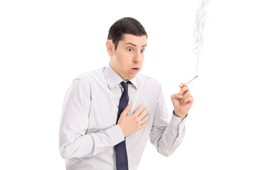 Man smoking a cigarette and feeling chest pain
