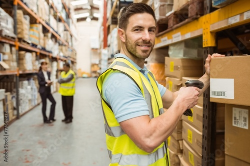 Warehouse worker scanning box while smiling at camera - 77369878