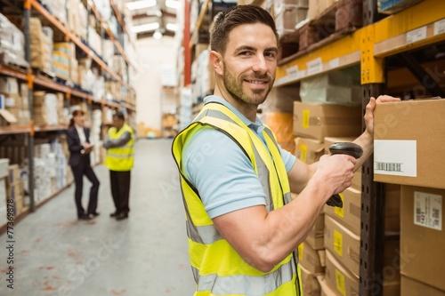 Leinwanddruck Bild Warehouse worker scanning box while smiling at camera