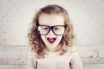 Laughing little funny girl wearing glasses