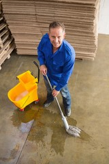 Smiling man moping warehouse floor