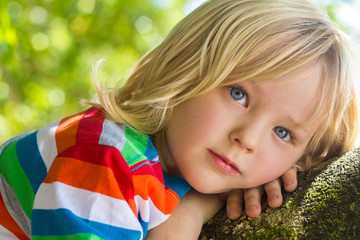 Cute child relaxing deep in thought in a tree