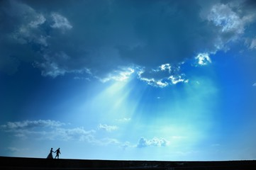 A couple in love in dramatic blue sky. Peaceful romantic moment.