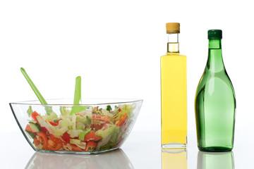 Eine Glaschale mit gemischtem Salat und Essig und Oel