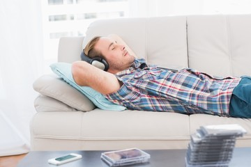 Man napping on sofa with music