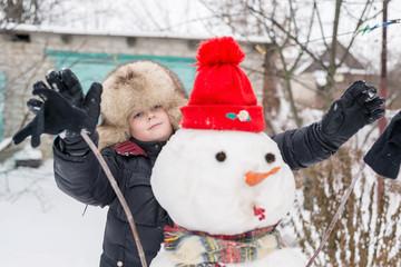The boy in a fur hat around snowman