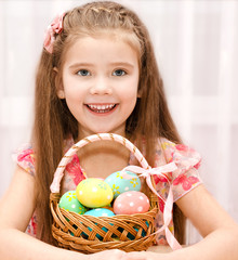 Cute smiling little girl with basket full of easter eggs