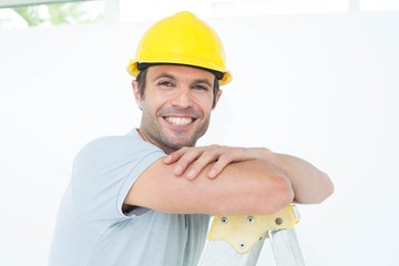 Happy technician leaning on step ladder