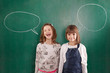 Girls standing in front of chalkboards with speach bubbles