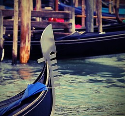 famous bow gondola in Venice  in the lagoon with other boats